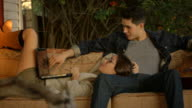 Young couple laying on couch hanging out
