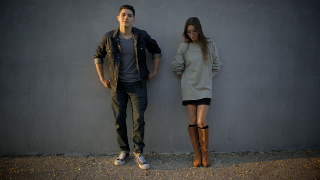 young couple leaning against wall
