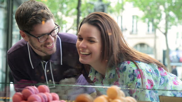 A couple admires macarons at a bakery in Paris.