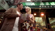 SLO MO, LA, MS, Young couple looking at map in Chinatown, New York City, New York, USA