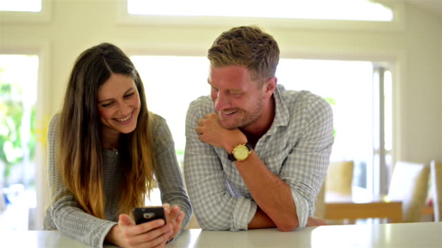 DOLLY SHOT: Young couple looking at pictures on smartphone