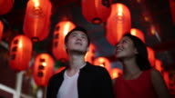 MS young couple looking at red lanterns at night.