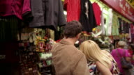 SLO MO, CU, Young couple looking at souvenirs on market stall and kissing, Chinatown, New York City, New York, USA