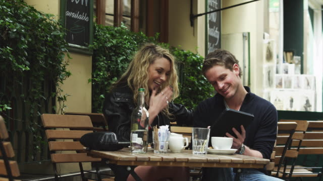 MS Young couple looking at tablet pc at outdoors cafe / London, UK