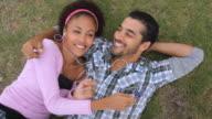 CU Young couple lying on grass listening music and sharing headphone / Havana, Cuba
