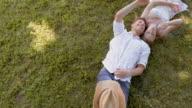 CS Giovane coppia sdraiarsi sull'erba e facendo bolle