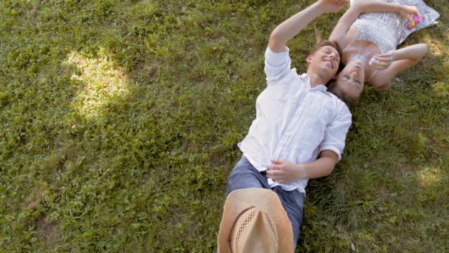 CS junges Paar liegen auf dem Rasen und macht Seifenblasen