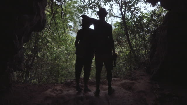 Young couple of traveler friends at the hole of a cave looking to outside. They wear adventure style outfit with hat. They have fun and do jokes. Rear point of view. Travel Like a Local - Brief
