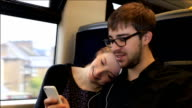 Young couple on a train, headphones,streaming video.