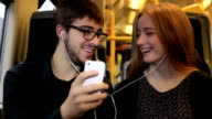 Young couple on a train listening to music.