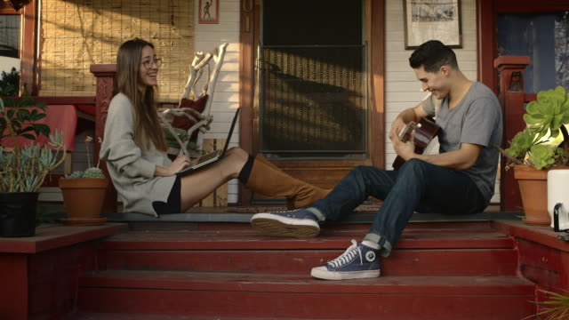 young couple on porch with computer and guitar