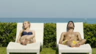 Young couple on sun loungers holding hands