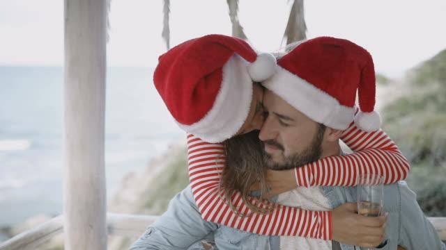 Jong (echt) paar op het strand met de kappen van de Kerstman