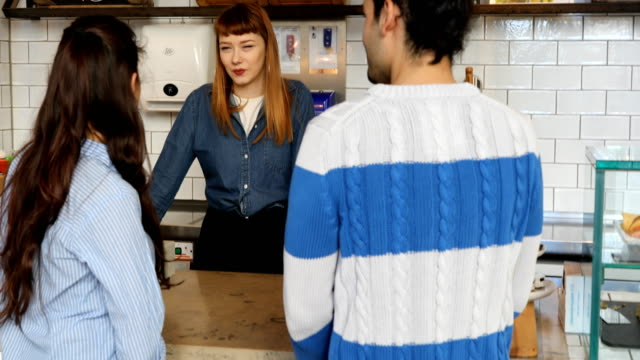 Young Couple Ordering To Female Barista At Cafe