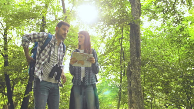 Young couple orienteering with help of a map and talking about direction they should go while exploring the nature.
