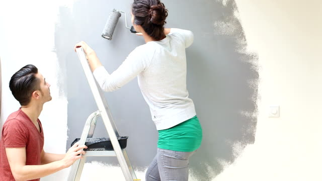 Young couple painting wall with paint roller