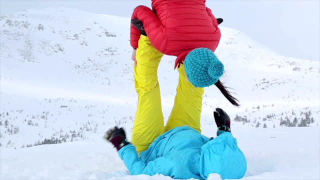 Young couple perform acrobatic yoga in the mountains