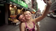 SLO MO, CU, Young couple photographing self in Chinatown, New York City, New York, USA