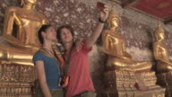 MS DS. Young couple photographing self in front of golden Buddha statue at Wat Phra Kaew (Temple of the Emerald Buddha), Bangkok, Thailand