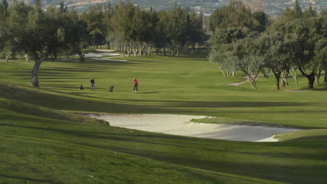 LS young couple playing golf along fairway towards camera, picking up their bags and walking in general camera direction, RED R3D 4K