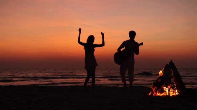 Young couple playing music with a guitar and dancing on the beach