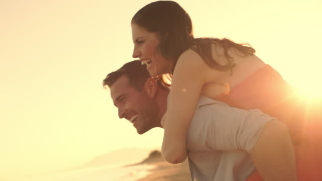 Young couple playing on beach in sunset, man carrying woman on his back.