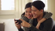 CU Young couple playing on smartphone at home