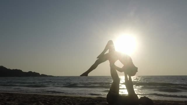 Young couple practice Acro Yoga on a beach - backbend