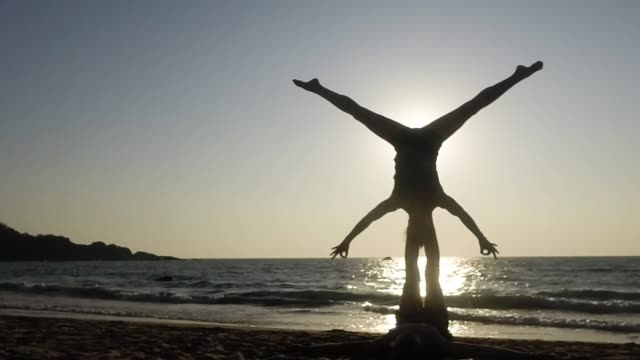 Young couple practicing Acro Yoga on the beach - star pose and exit