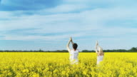 HD: Young Couple Practising Yoga In The Canola Field