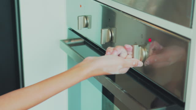 Young couple puts bread in oven