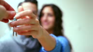 Junges Paar empfangen Autoschlüssel von Immobilienmakler
