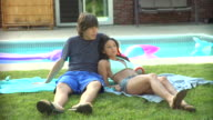 MS, Young couple relaxing beside pool, Middlesex, New Jersey, USA