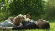 MS Young couple relaxing on lawn in Green Park / London, UK