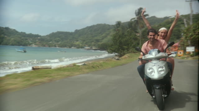 WS SLO MO POV Young couple riding on scooter / Scarborough, Tobago, Trinidad And Tobago