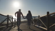 Young couple running down to beach on wooden causeway past camera