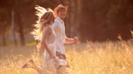 SLO MO TS Young couple running in high grass