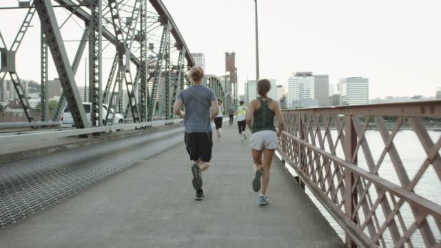 UHD 4K: SLO MO Young couple running over bridge