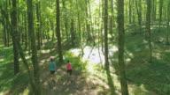 AERIAL junges Paar läuft durch den Wald
