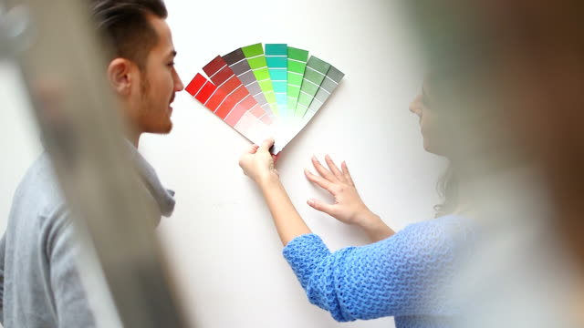 Young couple selecting paint colour in new home