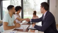Young couple shaking hands with a personal banker at a meeting in their home
