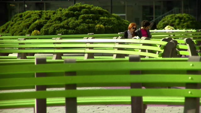 MS Young couple sit among a sea of green park benches and looking at guidebook at the park at the International Court of Trade/ New York City