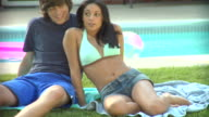 MS, Young couple sitting beside pool, Middlesex, New Jersey, USA