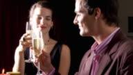 MS TU ZI Young couple sitting in bar and drinking champagne, woman kissing man / Sherman Oaks, California, USA.