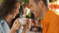 Young couple sitting in cafe laughing together.