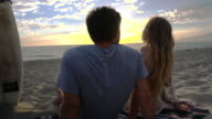 MS POV Young couple sitting on beach watching beautiful sunset and kissing at Santa Monica / Venice, California, United States