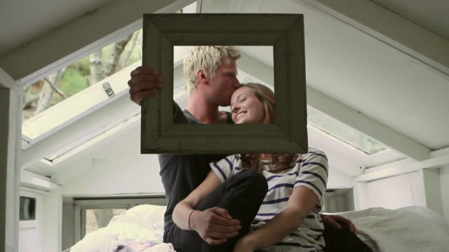 MS Young couple sitting on bed holding picture frame in front of them / Big Sur, California, USA