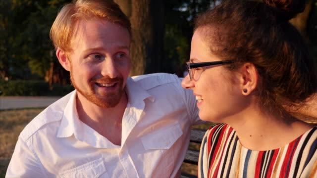Ungt par sitter på bänken och pratar i park