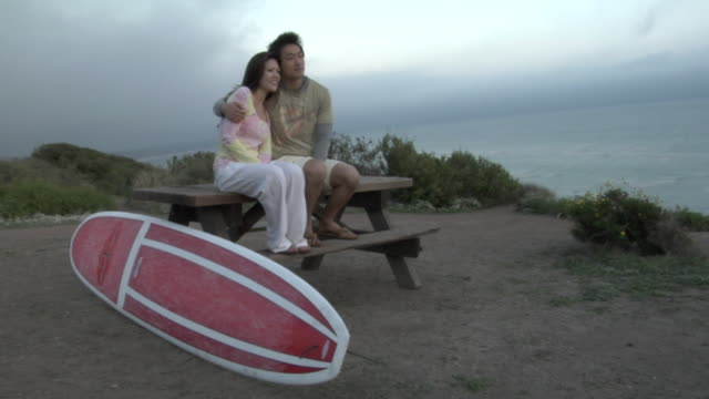 WS, Young couple sitting on picnic table on beach at sunset, Los Angeles, California, USA