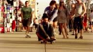 Young Couple Skateboarding Venice Beach Los Angeles.